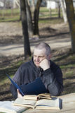 Tired man reading a book outdoors Stock Image