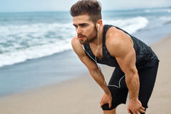 Tired Man Resting After Running On Beach. Sports Workout Outdoor. Portrait Of Athletic Man With Fit Muscular Body Resting After Jogging On Beach. Tired Exhausted Stock Images