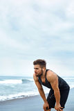 Tired Man Resting After Running On Beach. Sports Workout Outdoor Stock Images