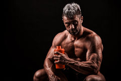 Tired man resting after training, holding bottle in hand. Royalty Free Stock Images