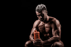 Tired man resting after training, holding bottle in hand. Stock Image