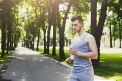 Tired man runner taking run break. Tired runner taking break in park. Athlete holding bottle of water, having rest after workout, copy space Royalty Free Stock Images