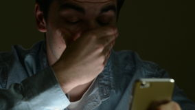 Tired Man Sending Text Message On Mobile Phone Late At Night. Camera tracks across face of tired young man who rubs his eyes as he sends text message on mobile stock video footage