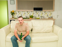 Tired man sitting alone on a couch Stock Image