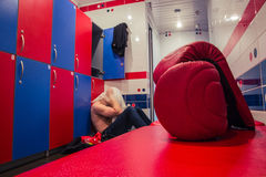 Tired man sitting on the floor in the locker room Royalty Free Stock Photos
