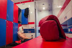 Tired man sitting on the floor in the locker room Royalty Free Stock Image
