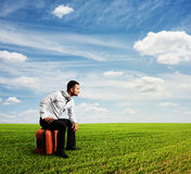 Tired man sitting on his bag Royalty Free Stock Photography