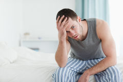 Tired man sitting on his bed Royalty Free Stock Photo
