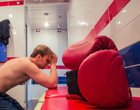 Tired man sitting in the locker room Royalty Free Stock Photo