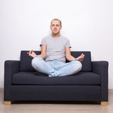 Tired man sitting on sofa in yoga pose Royalty Free Stock Photos