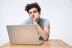 Tired man sitting at the table with laptop Stock Photo