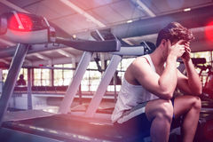 Tired man sitting on treadmill Royalty Free Stock Photography