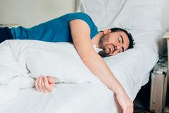 Tired man sleeping in bed in the morning Stock Photography