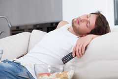 Tired man sleeping on couch. In front of tv Royalty Free Stock Photography
