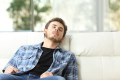 Tired man sleeping on a couch. Front view of a tired man sleeping on a couch at home Royalty Free Stock Photo