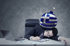 Tired man sleeping on desk with bomb on head Stock Image