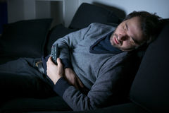 Tired man sleeping in front of the tv screen stock photo