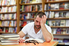 Tired man sleeping in the library Stock Photo