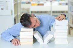 Tired man sleeping on pile books Royalty Free Stock Image