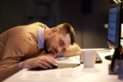 Tired man sleeping on table at night office. Business, overwork, deadline and people concept - tired man sleeping on table at night office Royalty Free Stock Photography