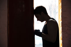 Tired man sportsman leaning on punchbag while training. Tired sportsman boxer leaning on red punchbag while training Royalty Free Stock Photos