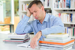 Tired man with stack books Royalty Free Stock Photo