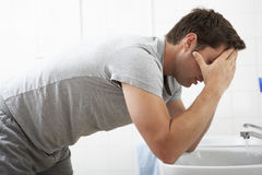 Tired Man In Standing At Bathroom Sink Stock Photo