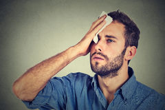 Tired man stressed sweating having fever headache. On gray wall background. Worried guy wipes sweat on his face Stock Photography
