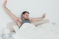 Tired man stretching his arms Stock Photo