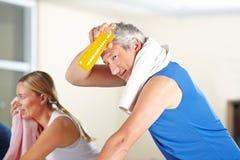 Tired man sweating in gym. Tired men with orange juice sweating in gym on spinning bike Stock Image