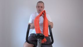 Tired man with a towel on exercise bike stock footage