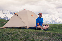 Tired man traveler sits next to the tent, in the mountains Stock Images
