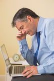 Tired man using a laptop sitting on a bed Royalty Free Stock Image