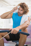 Tired man using resistance band in gym Stock Photography