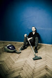 Tired man with vacuum, resting Stock Images