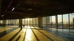 A tired man walk in business building inside platform,sunset rays light pass window. stock video footage