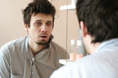 Tired man who has just woken up looks at his reflection in the mirror and sees his scruffy appearance. Dressed in a plaid shirt royalty free stock photos