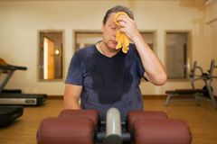 Tired man wiping sweat after workout Royalty Free Stock Photos