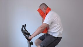 Tired man wiping with towel on exercise bike stock footage