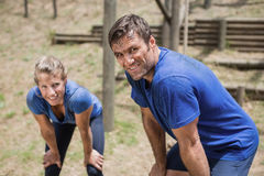 Tired man and woman bend down with hands on knees during obstacle course Royalty Free Stock Photography