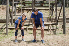 Tired man and woman bend down with hands on knees during obstacle course Stock Images