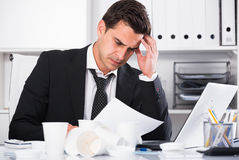 Tired man working in hot office. Tired man with loosened tie and disposable cup working in hot office Stock Photo