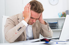 Tired man working in office stock photography