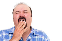 Tired man yawning. With his hand to his mouth as he tries to fight off his exhaustion, isolated on white Stock Image