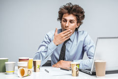 Tired man yawns and covers her mouth with her hand. / modern office man at working place, depression and crisis concept Royalty Free Stock Photo