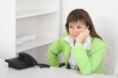 Tired manager reflects at office sitting at table. The tired manager reflects at office sitting at a table stock photo