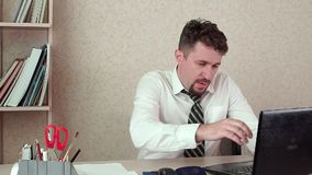 Tired manager working on a laptop. He`s in the office tired and wants to go home. Tired manager working on a laptop. He`s in the office, tired and wants to go stock video footage