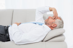 Tired mature businessman resting on sofa in living room Royalty Free Stock Photography