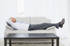 Tired mature businessman sleeping on sofa in living room Stock Image