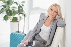 Tired businesswoman waiting for trip. Tired mature businesswoman with flight ticket and luggage waiting for trip Stock Photos